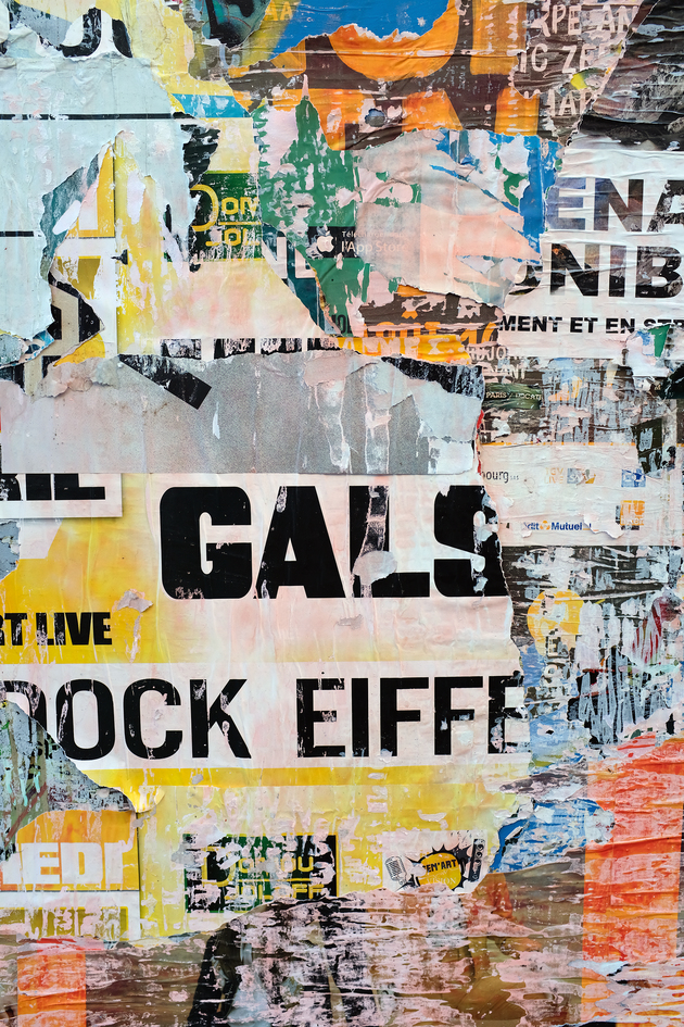 Posters on a grey concrete wall with 'GALS' in large, black letters in the middle
